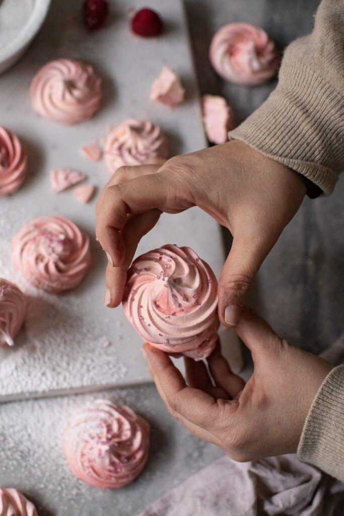 Meringhe rosa con polvere di lamponi e ripieno di crema al rum