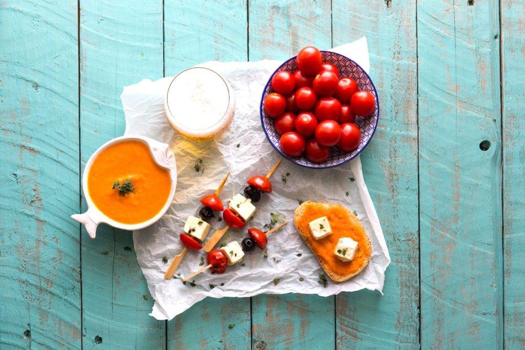Spiedini di feta pomodorini e olive nere su bruschetta di crema di peperoni e pomodori al timo